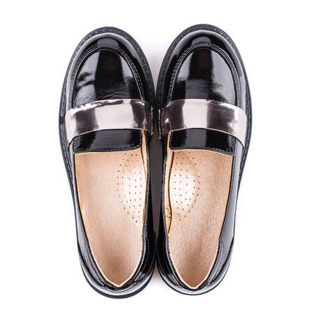 Lacquered shoes with silver inserts for girls on a white background. Photo for shoes advertisement. Top view
