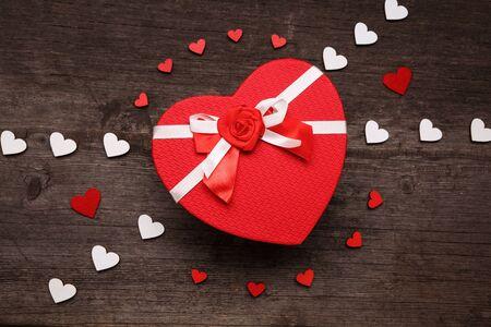 Het deksel van de doos in de vorm van een hart. Samenstelling met rode en witte hartjes op een houten ondergrond. Valentijnsdag concept met hartjes en geschenkdoos. Bovenaanzicht Stockfoto