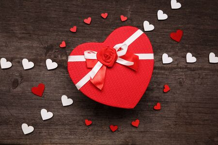 The cover of the box in the shape of a heart. Composition with red and white hearts on a wooden background. Valentines day concept with hearts and gift box. Top view