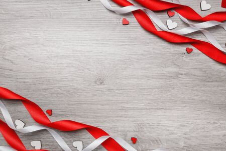 Red ribbon in the form of a spiral and decorative heart.. Mothers day. Womens day. Valentines day, Birthday greeting concept background. top view, flat lay
