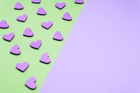Flat lay love background. Violet and green background. Violet wooden hearts on a green background. Love and holiday greeting concept background. Symbol of love.