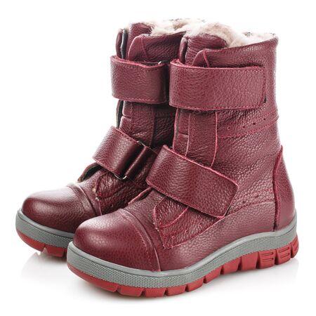 Botas de invierno para niños de color rojo para niñas sobre un fondo blanco. Foto para publicidad de zapatos
