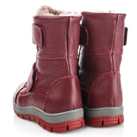 Red childrens winter boots for girls on a white background. Photo for shoes advertisement
