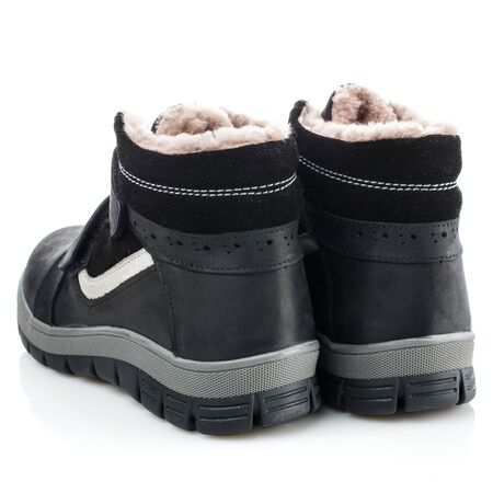 Black baby winter boots for a boy on a white background. Photo for shoes advertisement