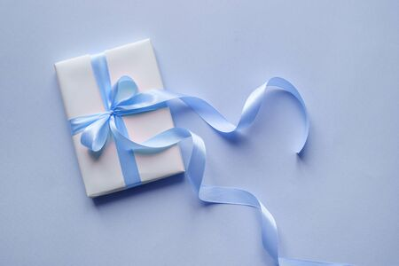 Decorative white gift box with blue bow and long beautiful ribbon on a blue background. Top view Stock fotó