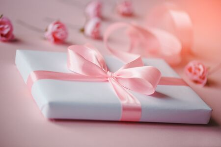 Composition of a white box and small pink flowers on a light pink background. Great beautiful pink ribbon bow. Packing of gifts