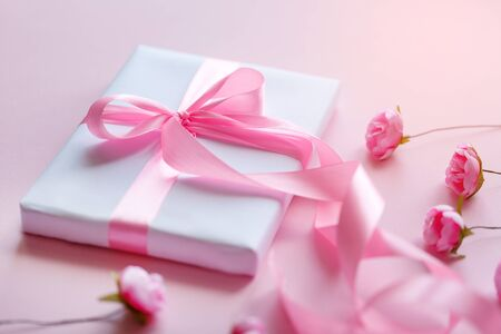 Spring decor from small pink roses. White gift box with a pink ribbon on a light background. Mothers Day.
