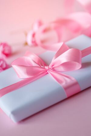 Decorative white gift box with pink bow and long beautiful ribbon on a pink background