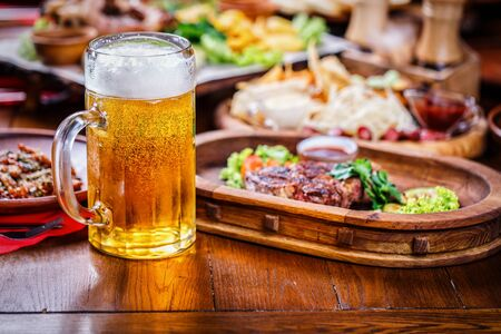 A glass of light beer on the background of a table with snacks. A glass of light beer with foam on a wooden table in the restaurant