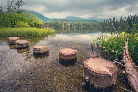 Mountain Lake in the High Tatras National Park. Strbske Pleso, Slovakia. A bridge in the form of wooden logs in a lake in the High Tatras.