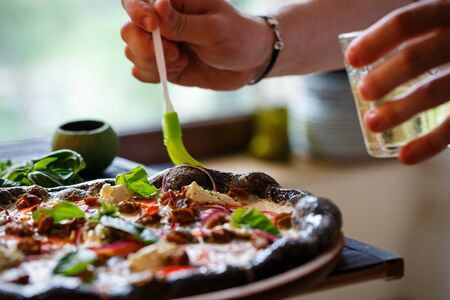Closeup hand of chef baker making pizza at kitchen. The cook lubricates the traditional Italian pizza with olive oil