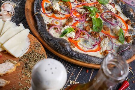 Italian pizza with black dough with cheese, pepper, onion and basil on a wooden tray. Ingredients of pizza on the foreground. Stock fotó