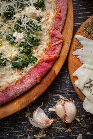 Close view of tasty appetizing classic italian traditional pizza. Food ingredients and spices for cooking pizza. Concept for a tasty and hearty meal. Rustic wooden background