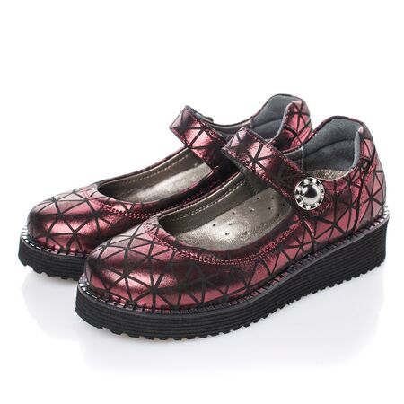 Zapatos infantiles de color rojo oscuro para niñas sobre un fondo blanco. Foto para publicidad de zapatos. Vista lateral