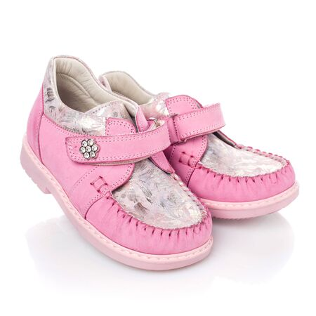 Zapatos infantiles de color rosa para niñas sobre fondo blanco. Foto para publicidad de zapatos