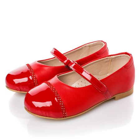 Children's red leather shoes for girls on a white background. Photo for shoes advertisement. Side view