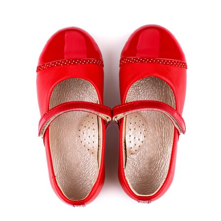 Children's red leather shoes for girls on a white background. Photo for shoes advertisement. Top view