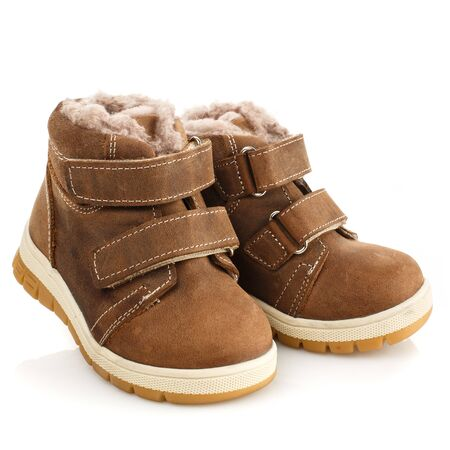 Children's brown winter boots with fur on a white background. Photo for shoes advertisement