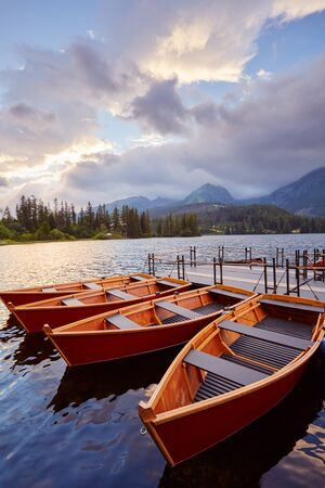Mountain Lake in the High Tatras National Park. Strbske Pleso, Slovakia. Berth with boats on a mountain lake in the rays of the sunset. Zdjęcie Seryjne