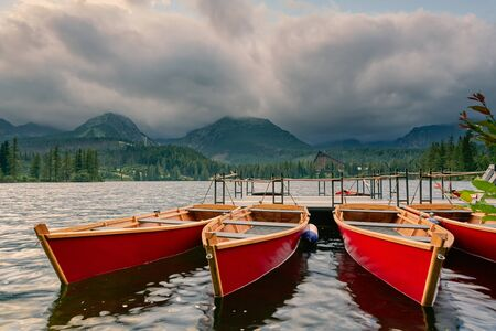 Mountain Lake in the High Tatras National Park. Strbske Pleso, Slovakia. Berth with boats on a mountain lake in the rays of the sunset.