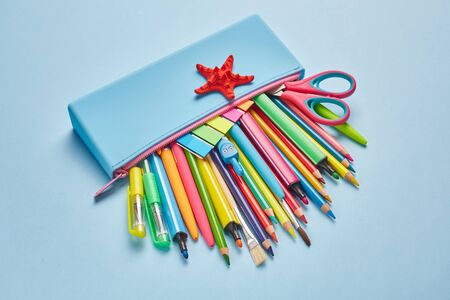 Blue pencil case with a red star on a light blue background. School objects for students