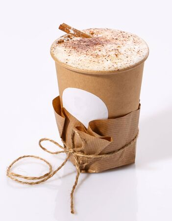 A Biodegradable Disposable Cup with blank white circle for text containing a hot drink on a white background with copy space.. Cinnamon coffee.