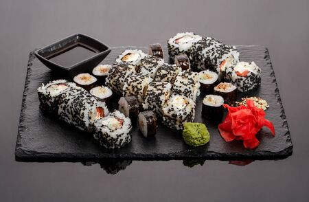 Originally put a set of sushi on a black board. With chopsticks, ginger, wasabi and soy sauce. Stok Fotoğraf