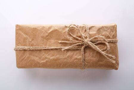 Gift wrapped in kraft paper and burlap ribbon on a white background. Top view.