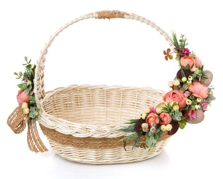 Very beautiful original wicker basket decorated with pink roses and greenery. Around the basket is a sack tape. Front view. Stock Photo