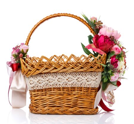 Easter basket. Brown wicker basket with colorful floral decor and colored ribbons on a white background. Beautiful basket design for Easter celebration. Spring colors Stock Photo