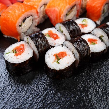 Various kinds of sushi served on stone background. Japanese sushi roles.