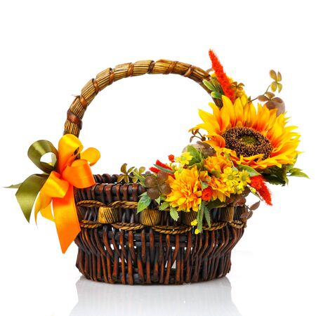 Original dark brown wicker basket with floral arrangements. Great scenery with yellow flowers, greenery and a large sunflower flower. Shopping cart in Ukrainian style. Isolated on white background. Side view.