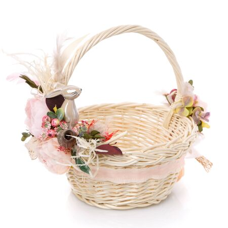 Wicker basket of natural vines with floral decor and ribbons on white background. The basket decor is made in delicate pink tones for Easter celebration. The decor uses natural materials and a small ceramic bunny.