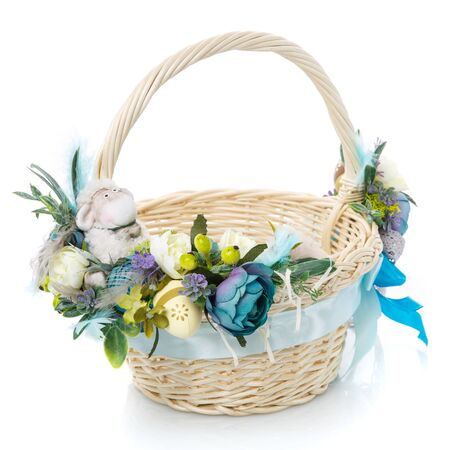 Easter basket on white background. Decorated with flowers in blue and a small decorative sheep. Ribbons and lace. Close up.