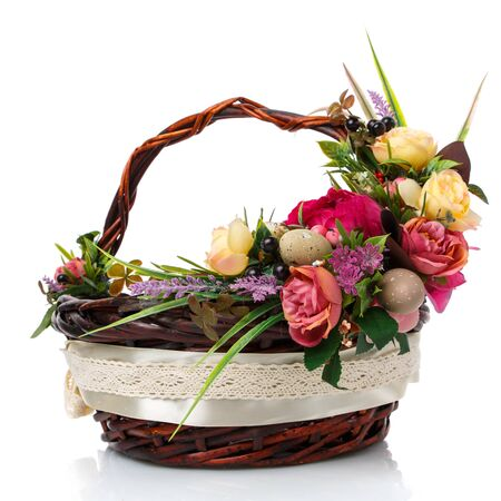 Dark brown wicker basket with original handle and floral decoration on a white background. Decor of yellow and pink flowers, green. wide ribbon and lace. Side view. Stock Photo