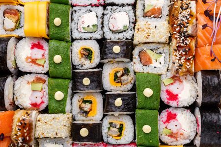 Assorted sushi set on stone background. Huge set of colored rolls with different stuffing. Salmon, tuna, eel, avocado, cucumber, Philadelphia cheese, cutlets and caviar. Close up view.