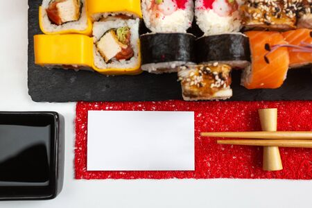 Different types of sushi rolls with a variety of stuffing on a dark stone board and soy sauce on a white table. Blank white card for text or inscription. Promotional shooting. Top view. Stock Photo