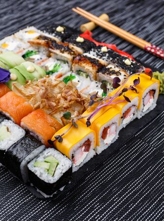 Sushi roll japanese food in restaurant on a stone board. Diferent Sushi roll set with different fish, vegetables, cheese, sesame, ginger and wasabi close up. Wooden sticks on gray background. Top view