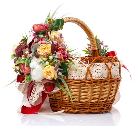 Provence Easter floral arrangement on a white wicker basket with a vine. Isolated. Ribbons and lace. Side view.