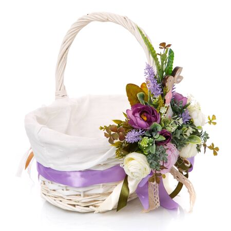White wicker basket with floral decoration, decorative wooden bunny and ribbons on white background. The basket is decorated in purple before Easter. Provence style.