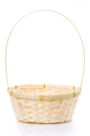 A small wicker basket made of vines with a tall handle on a white background.