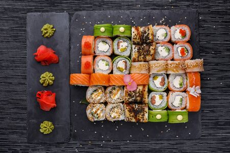 Japanese sushi food. Maki ands rolls with tuna, salmon, shrimp, crab and avocado. Top view of assorted sushi. Rainbow sushi roll, uramaki, hosomaki and nigiri.