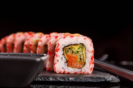 Japanese sushi with soy sauce and chopsticks on black background. Close up.