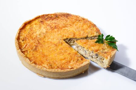 Delicious baked pie with meat, mushrooms, cheese and herbs on a white background. French pie. Stock Photo