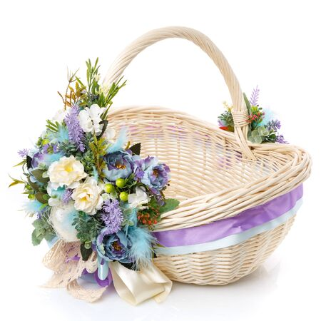 Brown wicker basket with floral decoration, decorative wooden bunny and ribbons on white background. The basket is decorated in in pastel colors before Easter. Provence style.