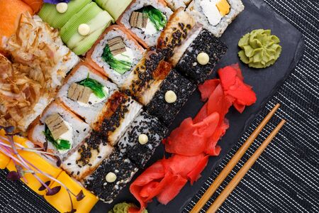 Different types of asian sushi rolls on gray background. Close up top view, flat lay with Japanese food.