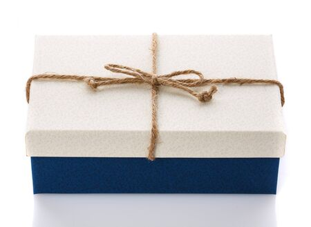 Cardboard box on a white background. Gift box with sacking ribbon. A modern gift for any holiday. Stock Photo