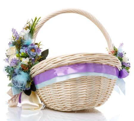 Provence Easter floral arrangement on a white wicker basket with a vine. Isolated. Easter Basket. Stock Photo
