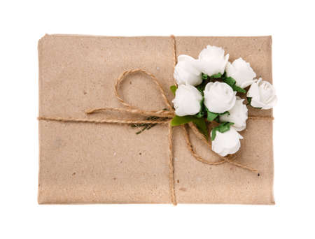 Festive gift box wrapped in kraft paper with burlap ribbon and white flowers on white background. 스톡 콘텐츠