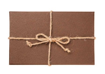 Brown festive gift box with burlap ribbon on white background. Top view.